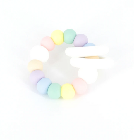 Ease your bubs teething with the Trio Teether- pastel rainbow by Lluie!  The TRIO teether features 2 silicone donut rings which circulate the larger beaded silicone ring