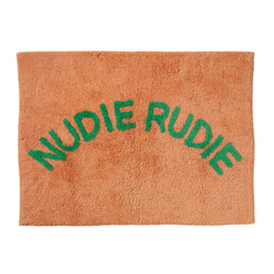 Cheeky 'Nudie Rudie' text adorns this tufted bath mat, adding a daily dose of fun to your bathroom.