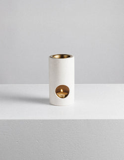 Designed with a minimal aesthetic the Limestone Synergy Oil Burner from Addition Studio features a brass dish and tea light holder.