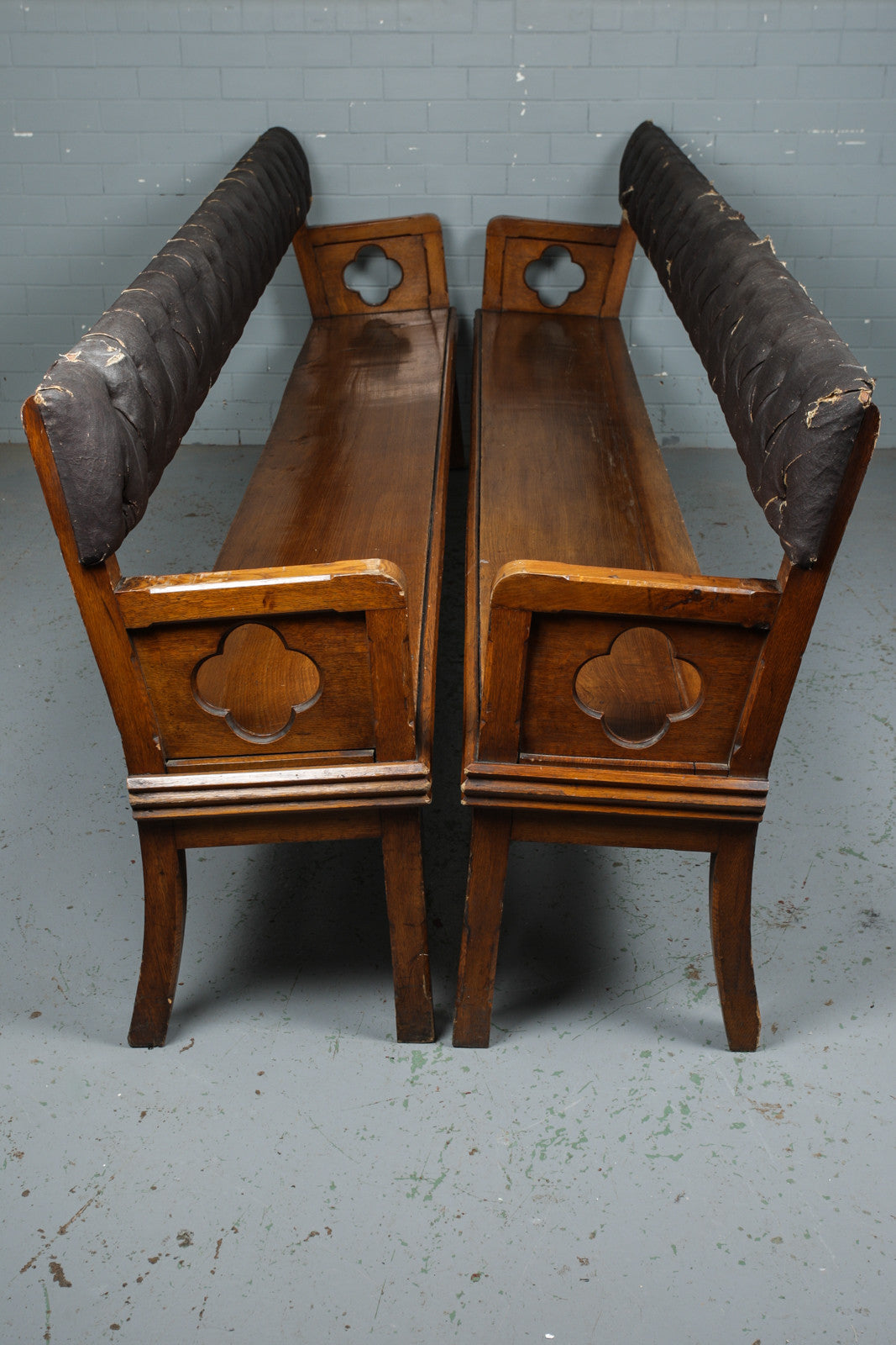 A pair of open backed solid oak and faux leather upholstered gothic revival style pews with quatrefoil carving. Avaialable to buy from Industrious Interiors, an online vintage furniture and homeware store based in Nottingham.