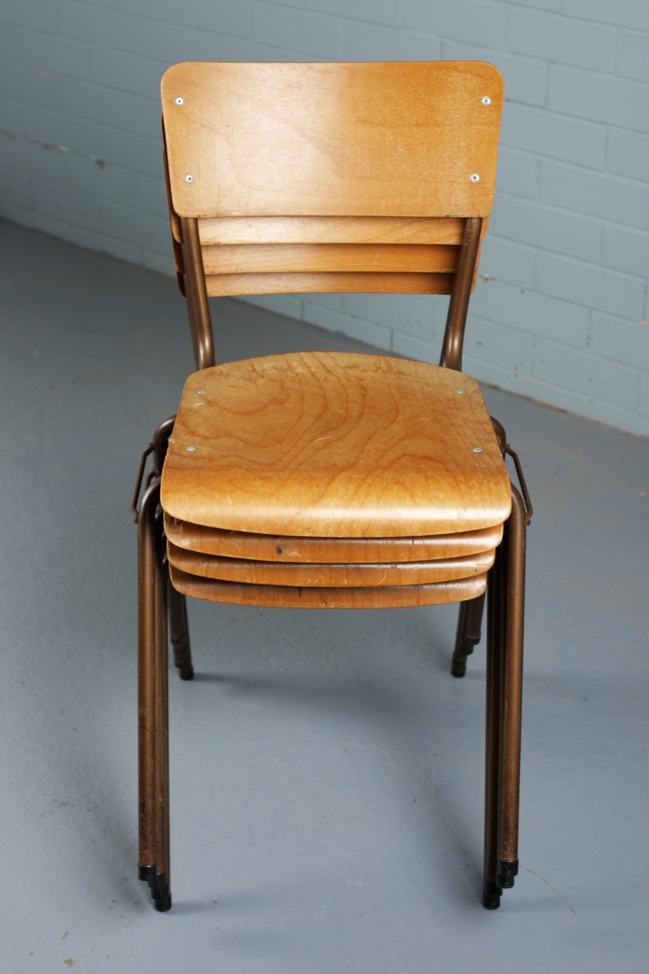 Tubular steel stacking chairs with bent plywood seat and back rest for sale at Industrious Interiors, an online vintage furniture and homeware store based in Nottingham, England.