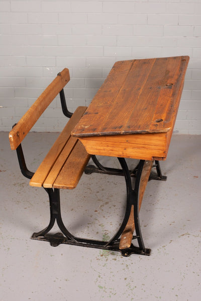 Oak double school desk with attached bench seat, under desk storage, cast iron legs and inkwell holes.