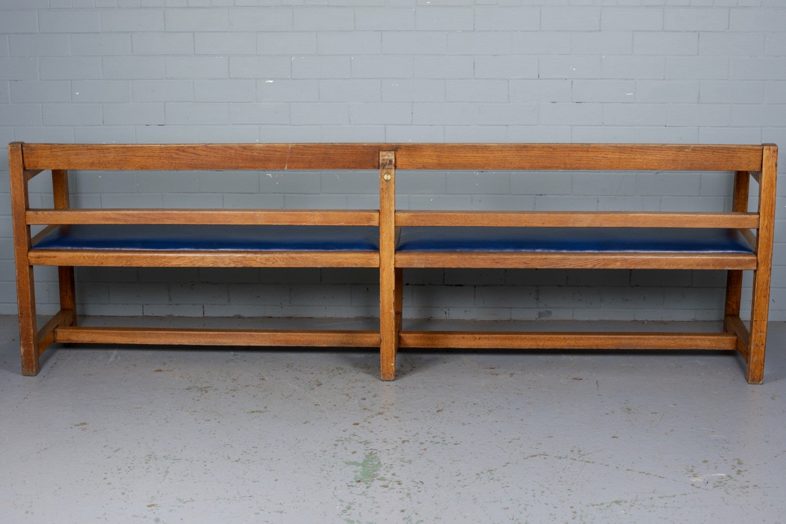 A 1940s large, double oak bench with a blue vinyl upholstered inlay for sale at Industrious Interiors, an online vintage furniture and homeware store based in Nottingham, England.