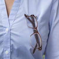 Swarovski Crystal Magnetic Eye Glasses Holder shown in use on a shirt by Readerest. Just Clip the magnetic backing and front hanger to your closes and hang your glasses. Also use to hold earphone cables and badges.