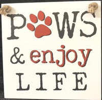 Sign - Paws and Enjoy Life 18cm x 18cm cream background with black and red writing.