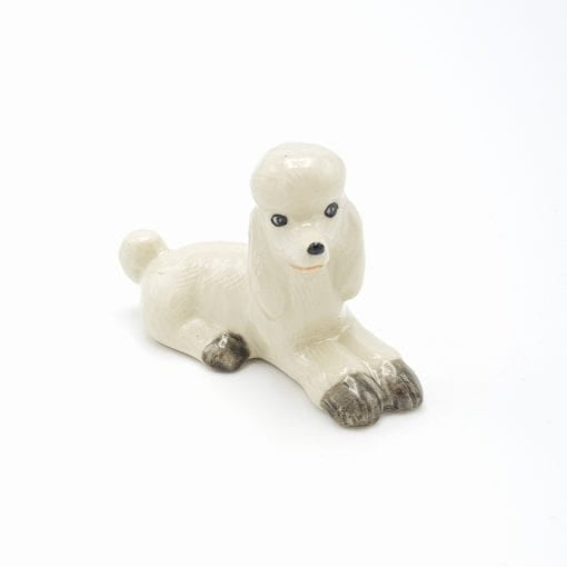 Laying white poodle figurine - A pretty white poodle with gray markings that is part of our extensive dog range.  As our ceramic animals are handcrafted and handpainted, size, colour and markings may vary.  This ceramic collectable figurine measures approx :  Laying 6.8cm x 3cm x 4.5cm high.  Made in Thailand.