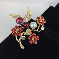 Beautiful brooch - crystal winged bird with red body on red flowers with a pearl on branch