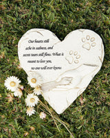 Memorial Stone heart shaped with paw prints and and a hand holding a paw. Saying ; Our hearts till ache in sadness, and secret tears till flow. What it meant to lose you, no one will ever know.