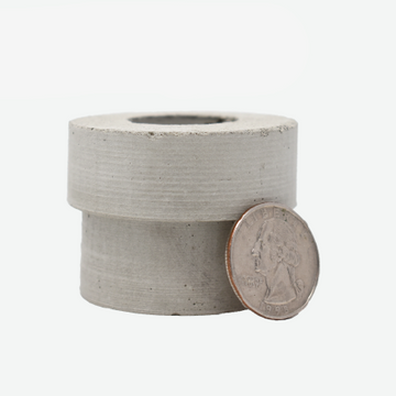 1:12 scale miniature concrete pipe with a quarter sitting on the side showing the scale