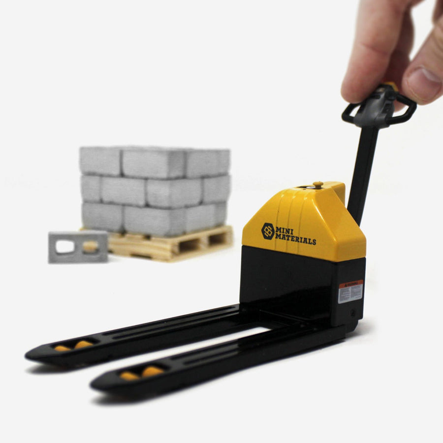 A miniature black and yellow pallet jack in the foreground with a pallet of mini cinder blocks blurry in the back.