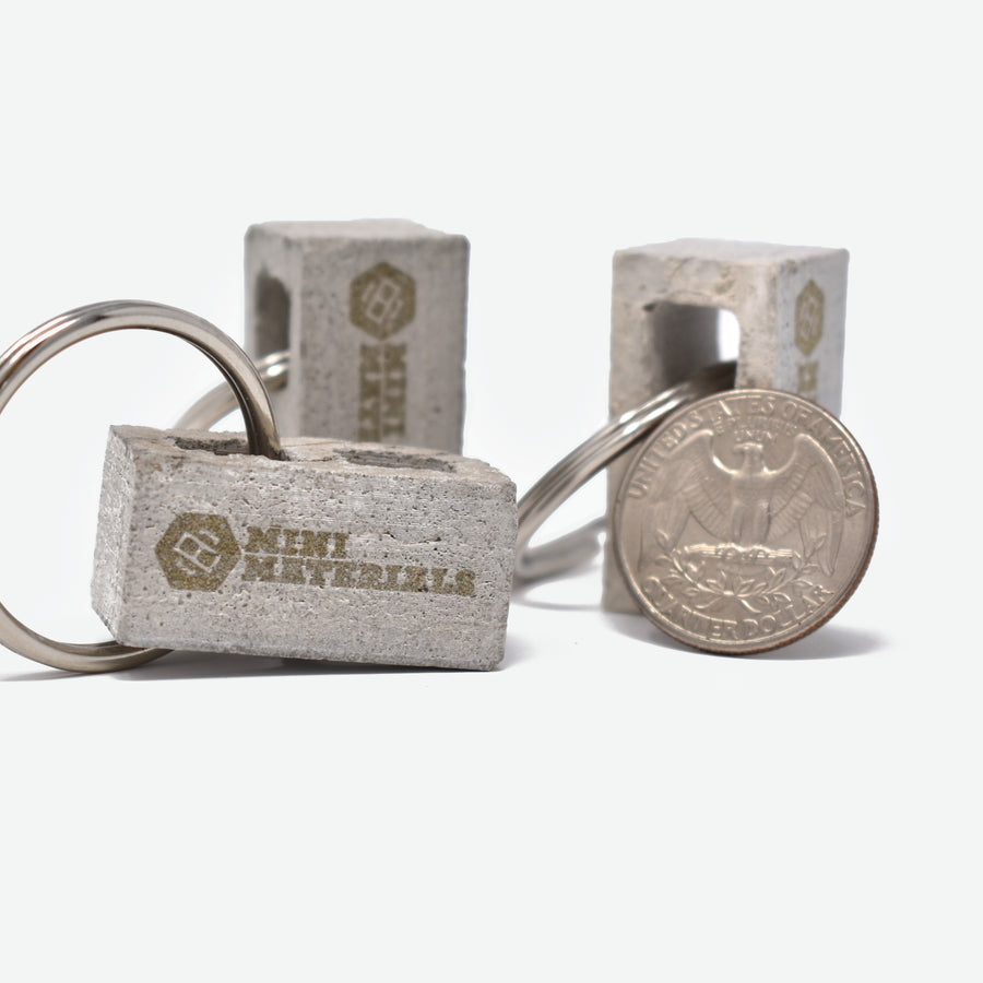 there are three 1:12 scale mini cinder blocks with the Mini Materials logo engraved on one side of each block. each mini cinder block has a silver colored metal key ring attached to it on one side through the hole in the block. a quarter is propped up on the far right mini cinder block to show scale