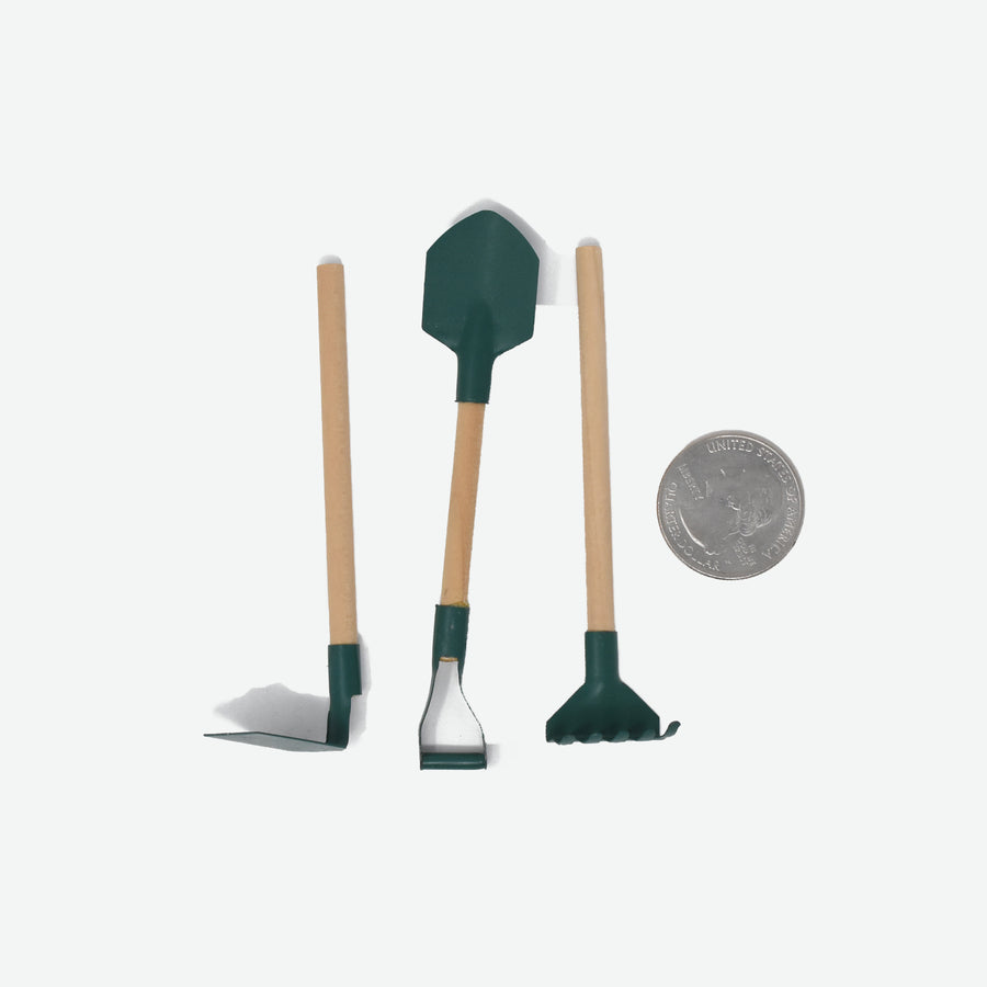 three miniature garden tools with wooden handles and a green metal detail and a quarter to show the scale. the garden tools shown are a spade, rake and a shovel.