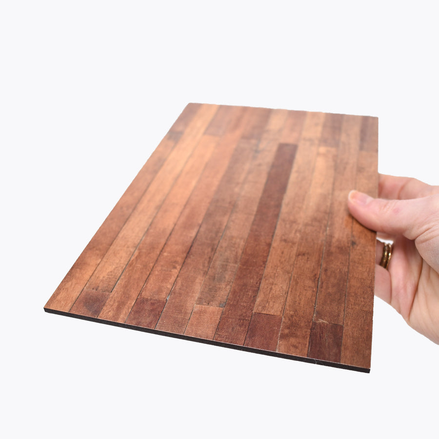 1:12 scale faux wood laminate with a hand holding it to show scale.