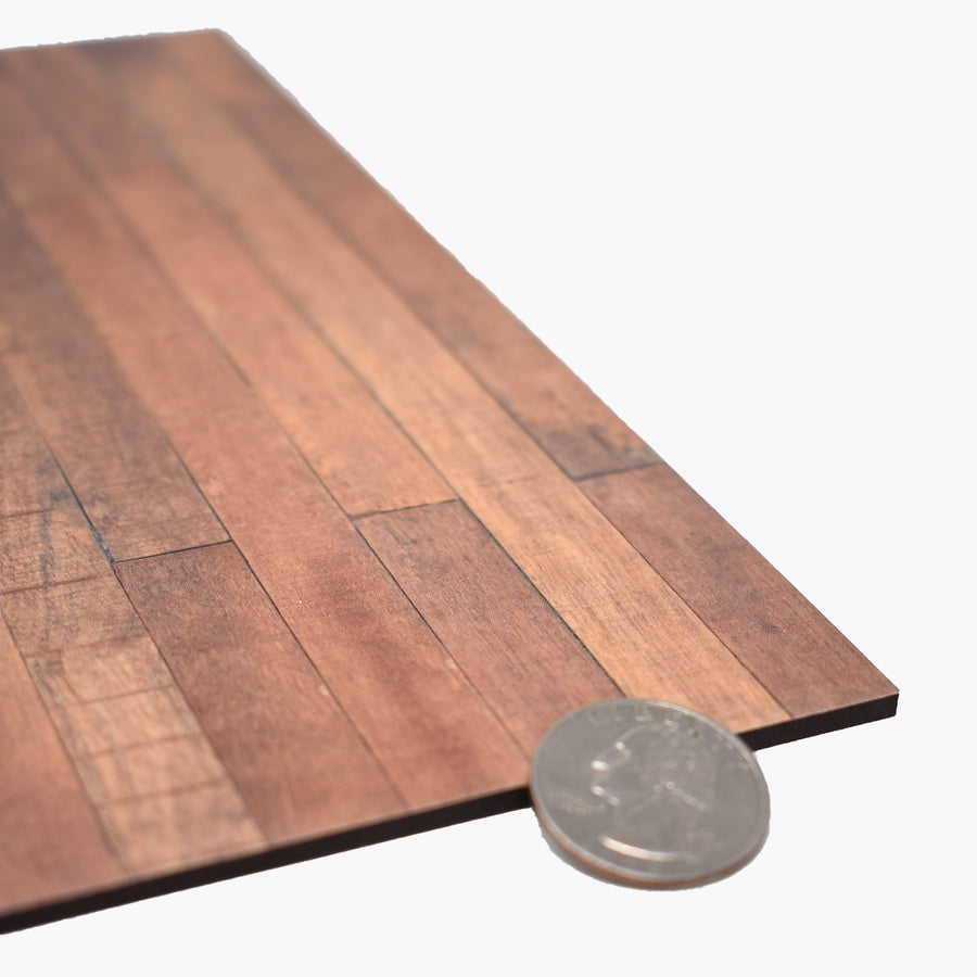 a close up photo of the 1:12 scale faux wood laminate with a quarter sitting to the right to show scale.
