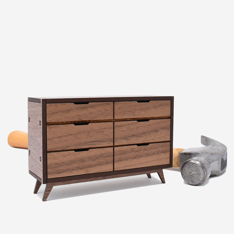 1:12 scale miniature mid-century dresser made of walnut wood. there is a hammer sitting behind the dresser to show scale.