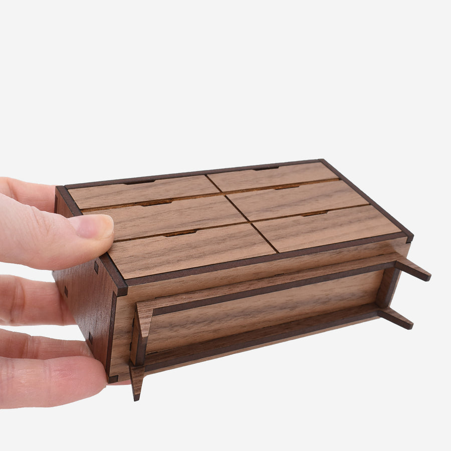 1:12 scale miniature mid-century dresser made of walnut wood. there is a hand holding the dresser on the left to show scale.