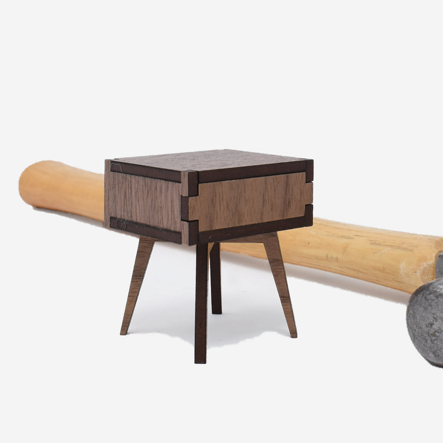 1:12 scale mid-century modern side table made of walnut wood with a hammer laying down behind the side table.