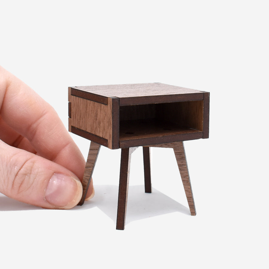 1:12 scale mid-century modern side table made of walnut wood with a hand holding onto one of the legs on the left side.
