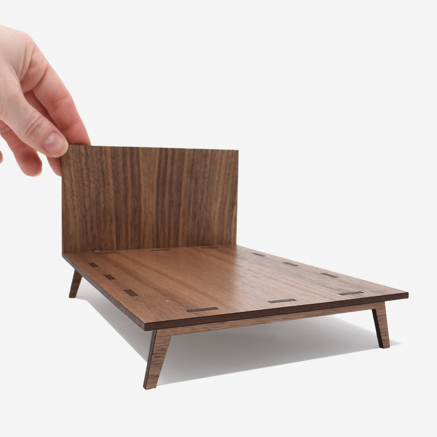 1:12 scale mid-century modern queen size bed made of walnut wood with a hand holding onto the left side of the headboard.