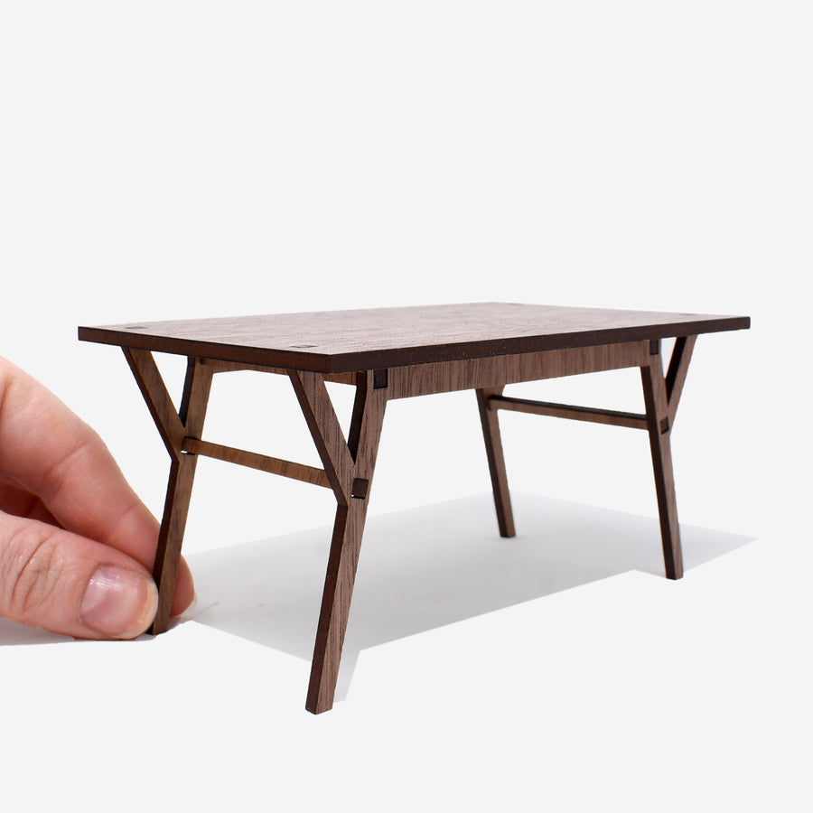 1:12 scale mid-century modern dining room table made of walnut wood. there is a hand holding the left side leg of the table to show scale.