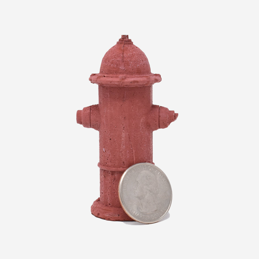 The back of a 1:12 scale miniature red-dyed concrete fire hydrant with a quarter sitting on the side showing the scale