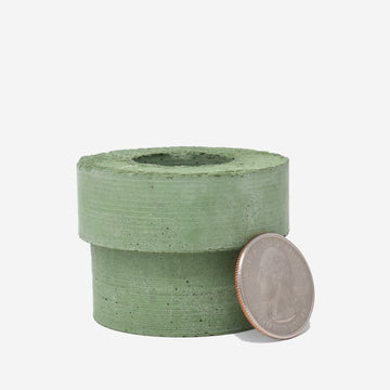 1:12 scale miniature green-dyed concrete pipe with a quarter sitting on the side showing the scale
