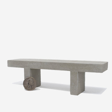 1:12 scale miniature concrete bench with a quarter sitting on the left hand side leg to show scale.