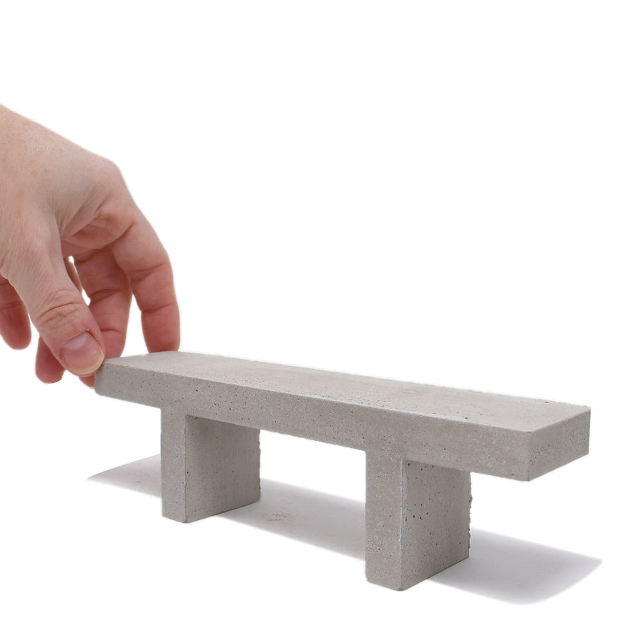 1:12 scale miniature concrete bench with a hand holding onto the left hand side to show scale.
