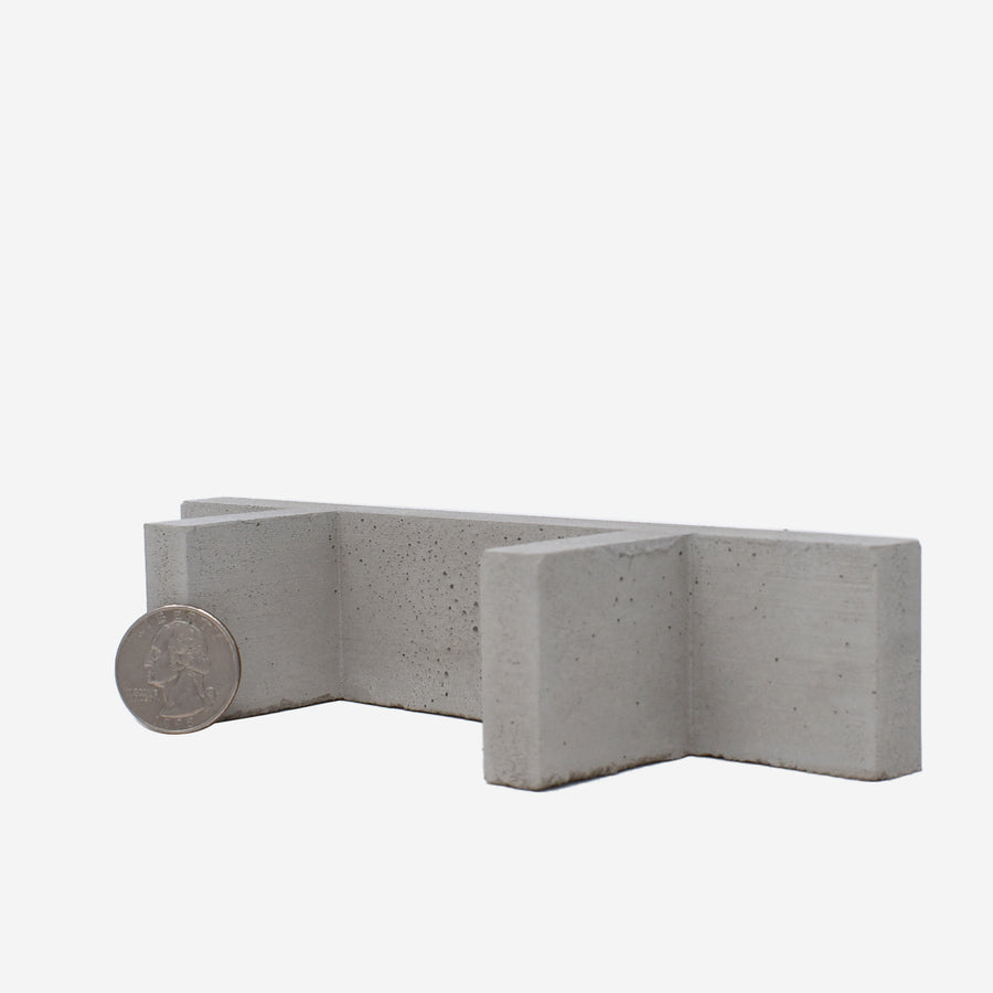The bottom of the 1:12 scale miniature concrete bench with a quarter sitting on the left hand side leg to show scale.