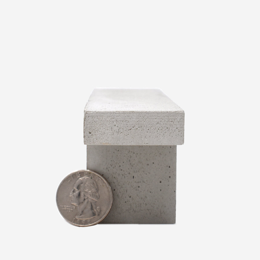 The end of a 1:12 scale miniature concrete bench with a quarter sitting on the left hand side of the leg to show scale.