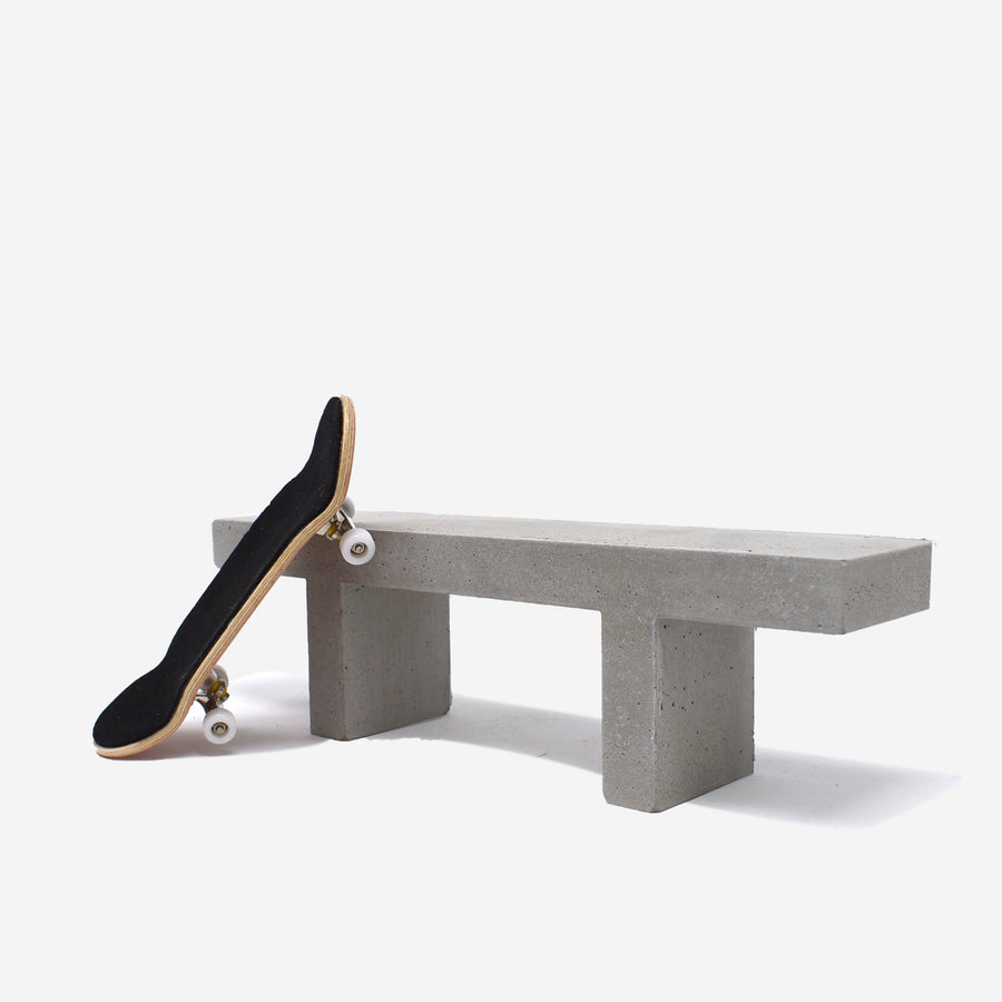 1:12 scale miniature concrete bench with a fingerboard sitting on the left hand side to show scale.