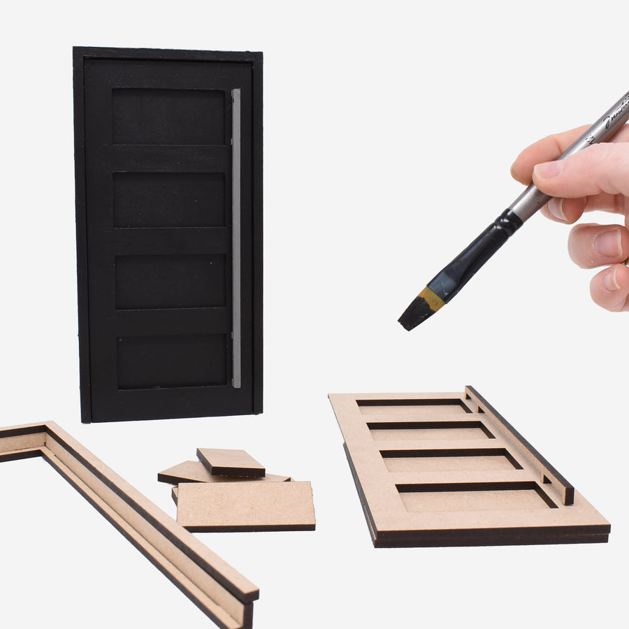 1:12 scale mid-century modern 4-panel door with long door handle and casement. There is a black painted version standing up behind the pieces that are laying down to show what the door would look like when it is painted. On the right side of the image there is a hand holding a silver paintbrush with black paint on it to represent being able to paint the doors.