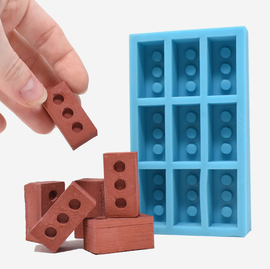 1:6 miniature red bricks laying in front of a 1:6 scale miniature red brick mold. The mold is aqua blue and can make 9 miniature red bricks. On the left side of the photo there is a hand holding one of the miniature red bricks to show scale.