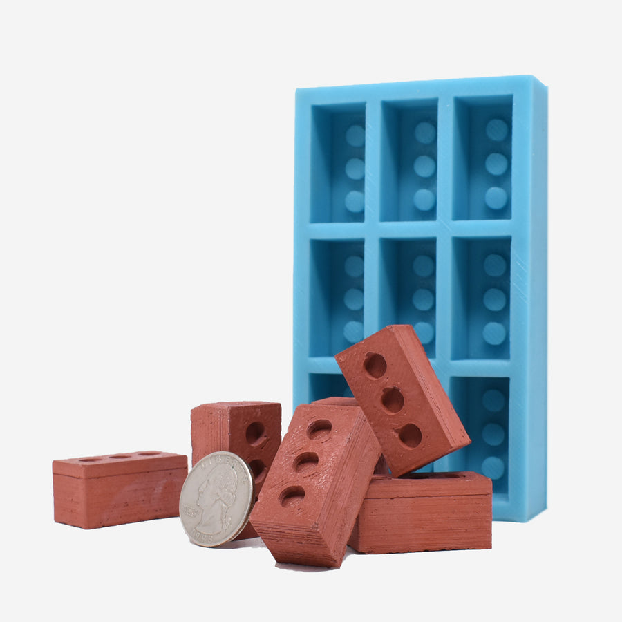 1:6 miniature red bricks laying in front of a 1:6 scale miniature red brick mold. The mold is aqua blue and can make 9 miniature red bricks. On the left side of the photo there is a quarter sitting against one of the miniature red bricks to show scale.