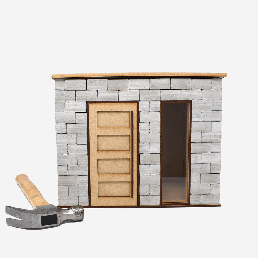 The front side of the 1:12 scale miniature cinder block build kit. A hammer is laying on the left of the kit to show scale.