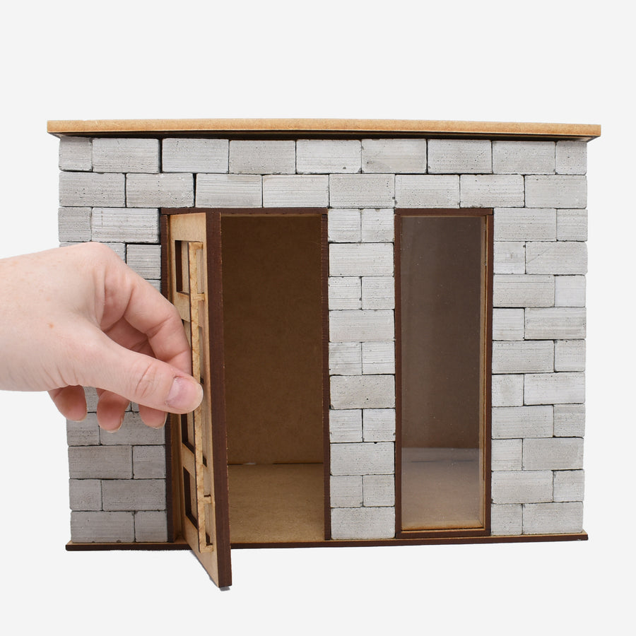 The front side of the 1:12 scale miniature cinder block build kit. A hand is opening the front door to show that it opens to show the inside of the build kit.