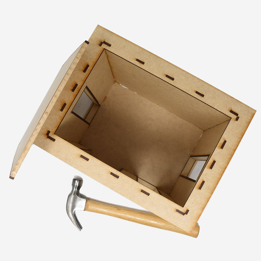 This is an image from above the build kit to show the interior of the kit. The lid is propped up on the left side of the kit and there is a hammer laying on the bottom to show scale.