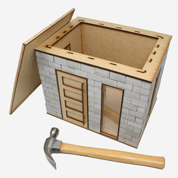 1:12 scale miniature cinder block build kit with an opening at the top. The lid of the kit is leaning on the left hand side of the kit and a hammer is laying in front of the kit to show scale.