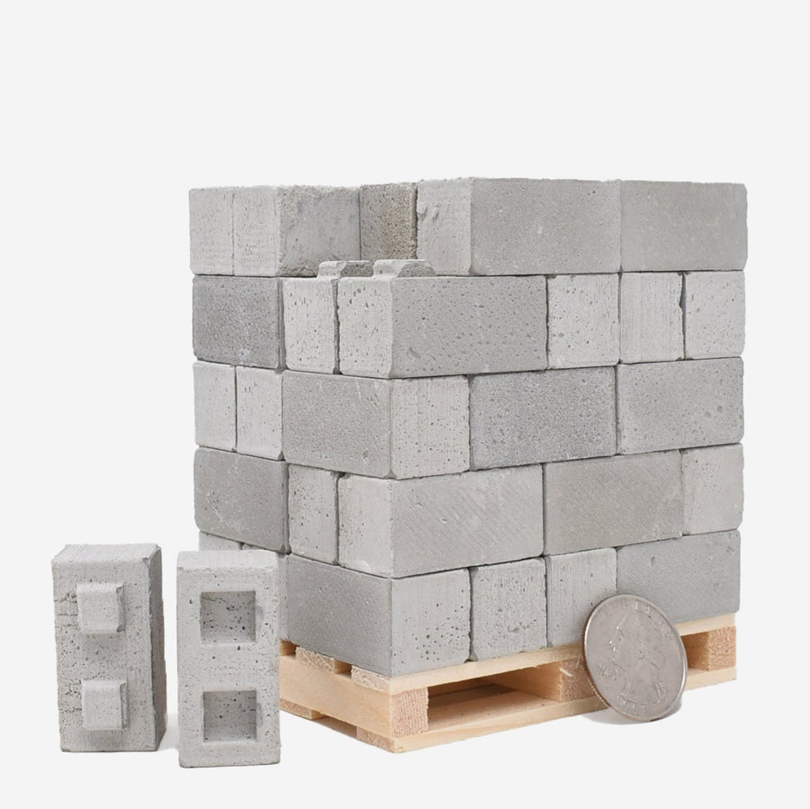 50 1:12 scale cinder blocks built up on a wood pallet with a quarter leaning against them on the right side for scale.