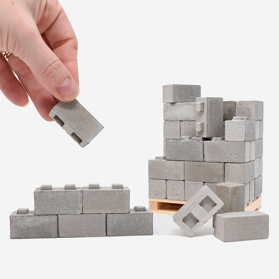 1:12 scale cinder blocks built up like a wall with a hand grabbing one of the blocks on the left side for scale. In the background on the right side there are more 1:12 scale blocks scattered on top of a pine wood pallet.