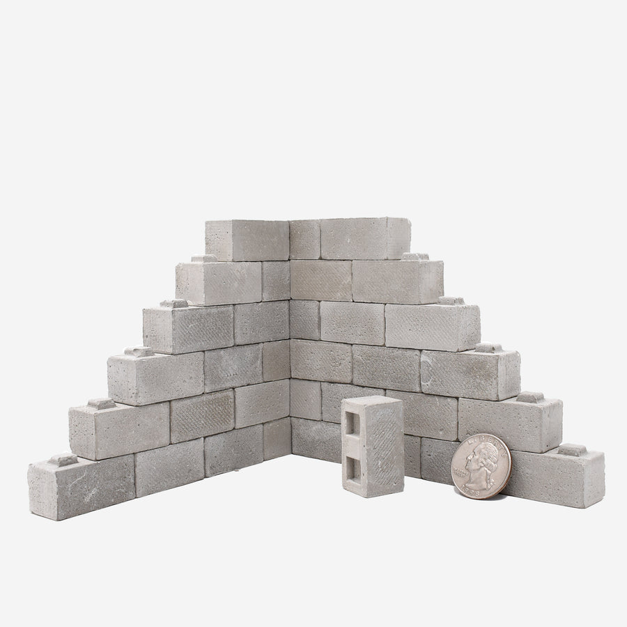 1:12 scale cinder blocks built up like a 2-sided wall with a quarter leaned up the bottom right side for scale.