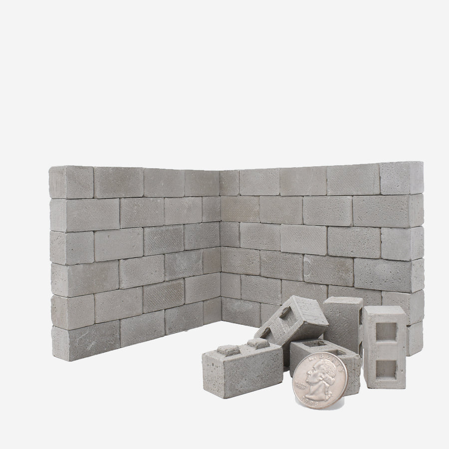 1:12 scale cinder blocks built up like a 2-sided wall with a quarter leaned up against a small pile of blocks on the bottom right side for scale.