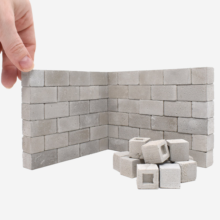 1:12 scale construct-a-block concrete blocks  built up like a 2-sided wall with a hand grabbing one in the top left corner for scale.