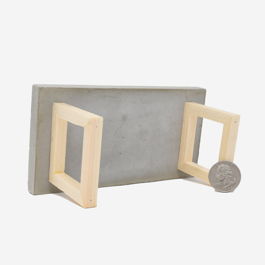 This is the bottom view of the 1:12 scale miniature table with concrete top and wooden legs. There is a quarter sitting up against the right leg to show scale.