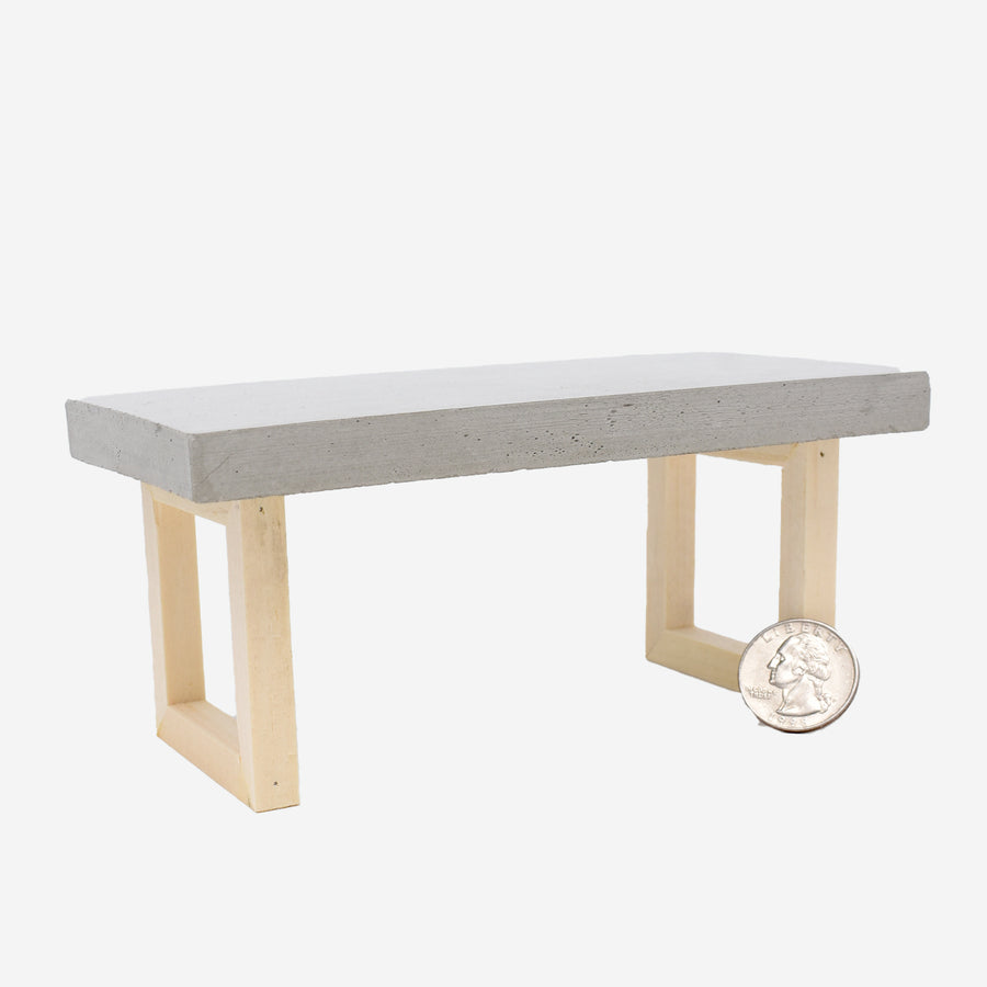 1:12 scale miniature table with concrete top and wooden legs. There is a quarter sitting up against the right leg to show scale.