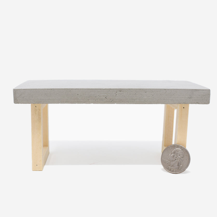 Front view of the 1:12 scale miniature table with concrete top and wooden legs. There is a quarter sitting up against the right leg to show scale.