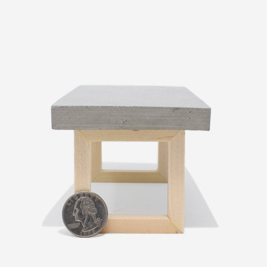 Side view of the 1:12 scale miniature table with concrete top and wooden legs. There is a quarter sitting up against the left side of the leg to show scale.