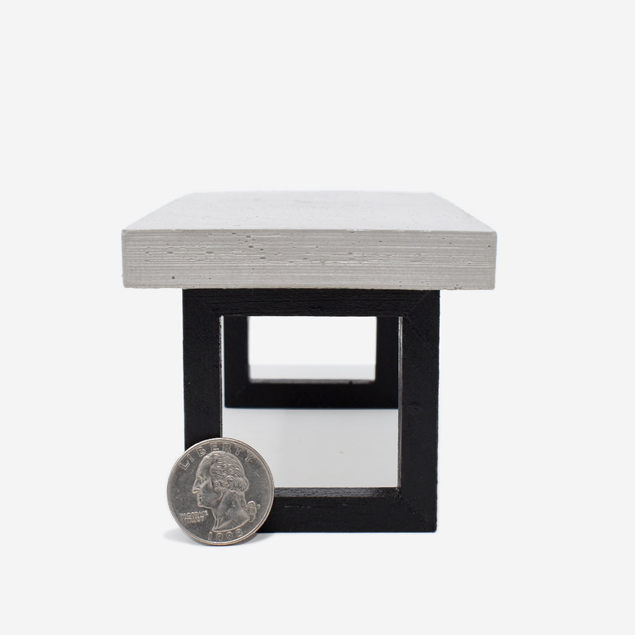 This shows the side view of the 1:12 scale miniature table with concrete top and wooden legs that have been painted black. There is a quarter sitting up against the left side of the leg to show scale.