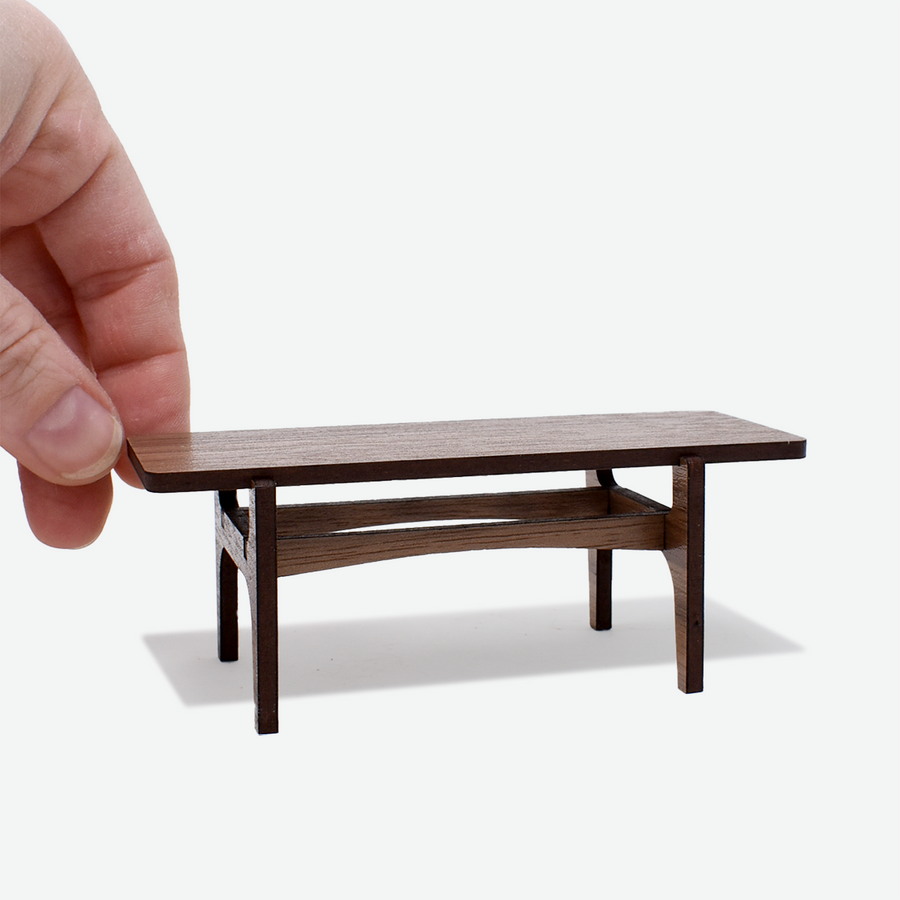 1:12 scale mid-century modern coffee table made of walnut wood with a hand holding onto the top on the left side.