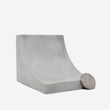1:12 scale miniature concrete quarter pipe with a quarter on the right side of the pipe